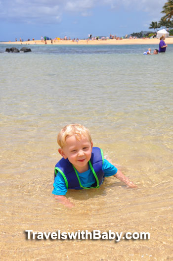 Toddler in water at Poipu Beach Park in Kauai, Hawaii