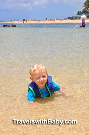 Toddler in water at Poipu Beach Park in Kauai, Hawaii