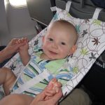 Baby not sleeping on an airplane, riding in the FlyeBaby air travel hammock.